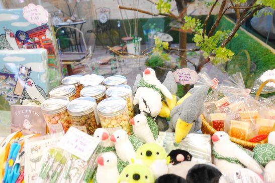 鳥用ガラスケージの前で鳥グッズ販売